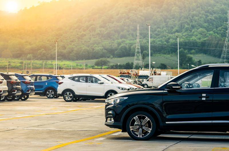 Zwarte, witte en blauwe nieuwe die auto op concreet parkeerterrein bij fabriek dichtbij de berg wordt geparkeerd Het concept van  royalty-vrije stock afbeeldingen