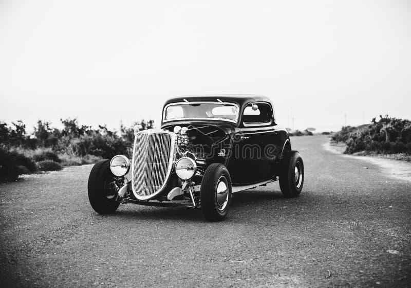 Zwarte & witte foto van een oude uitstekende die auto in het midden van de snelwegweg wordt geparkeerd stock fotografie