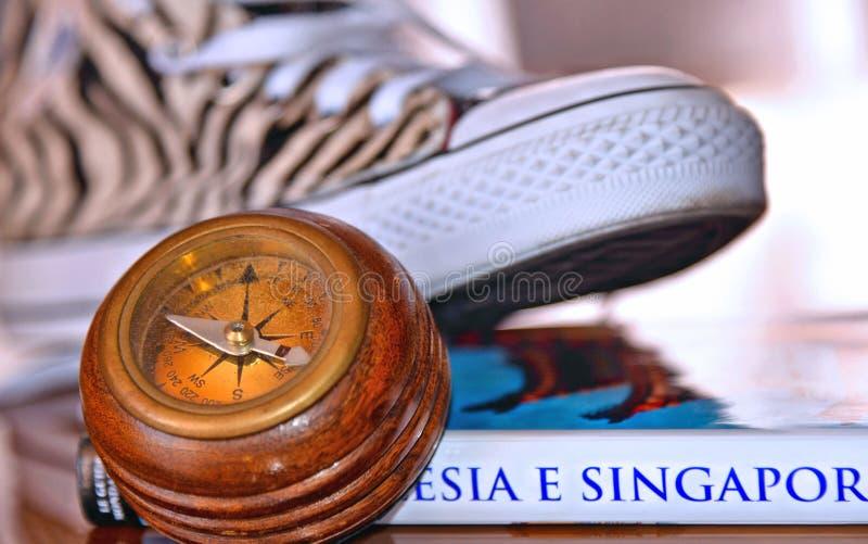 Zwarte Witte Gestreepte tennisschoenen All Star, uitstekende kompas en boekgids van Singapore, reisconcept, Parma Italië royalty-vrije stock afbeeldingen