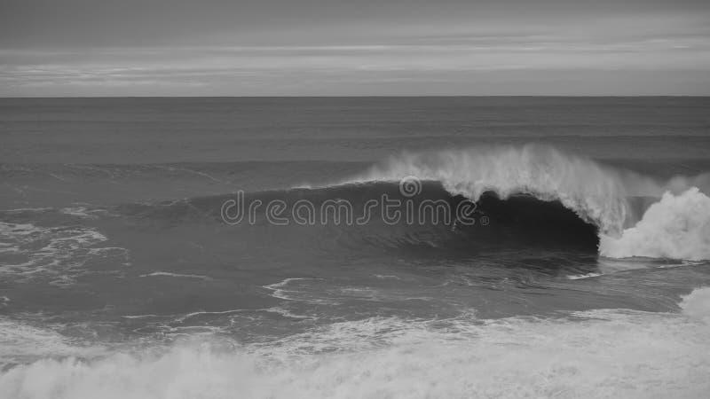 Zwarte & witte oceaan en golven die op een bewolkte dag verpletteren stock foto