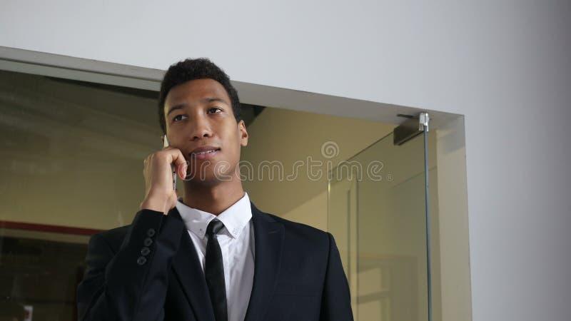 Zwarte Zakenman Attending Phone Call, voor Bureaudeur stock footage
