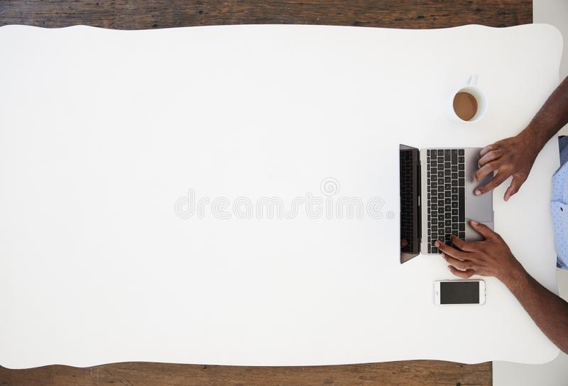 Zwarte zakenman die laptop met behulp van bij een geschoten bureau, boven royalty-vrije stock foto