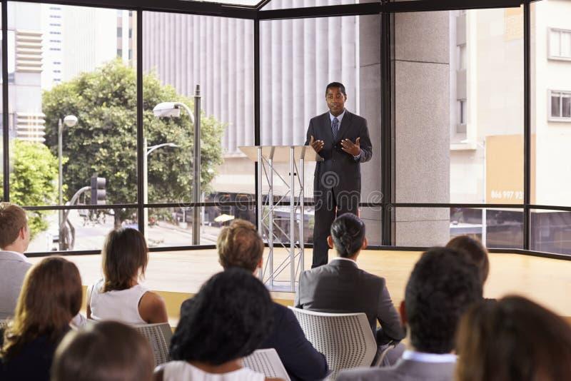 Zwarte zakenman die seminarie het gesturing voorstellen aan publiek stock foto