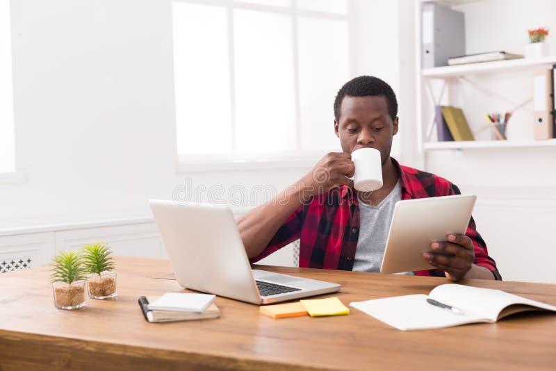Zwarte zakenman die in toevallig bureau, nieuws op tablet lezen, drinkend koffie royalty-vrije stock fotografie