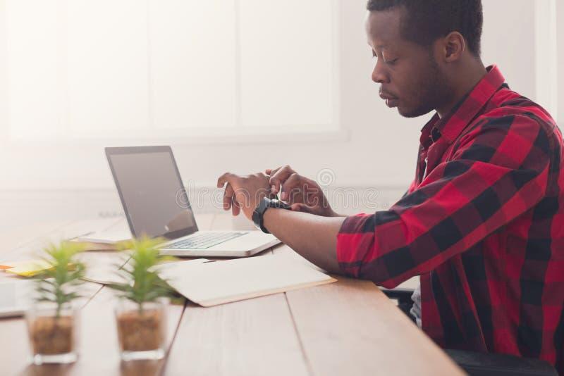 Zwarte zakenman in toevallig bureau, het werk met laptop royalty-vrije stock fotografie