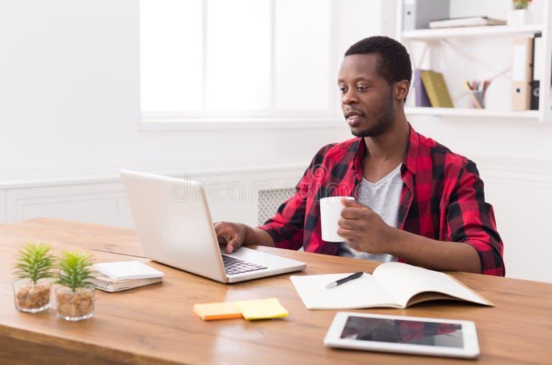 Zwarte zakenman in toevallig bureau, het werk met laptop stock foto