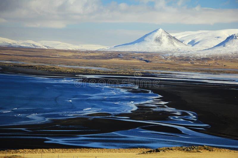 Zwarte zandstrand en sneeuw moutains in IJsland stock afbeeldingen