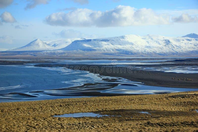 Zwarte zandstrand en sneeuw moutains in IJsland stock fotografie