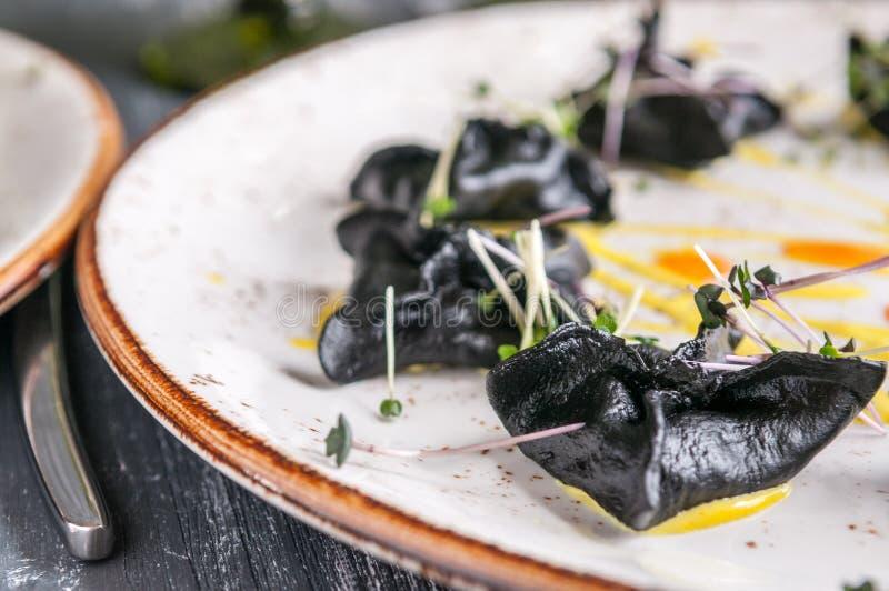 Zwarte zeevruchtenravioli op een donkere houten achtergrond royalty-vrije stock afbeeldingen