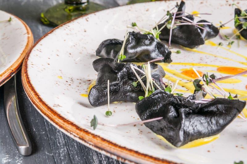 Zwarte zeevruchtenravioli op een donkere houten achtergrond Close-up, macro, vage achtergrond stock foto