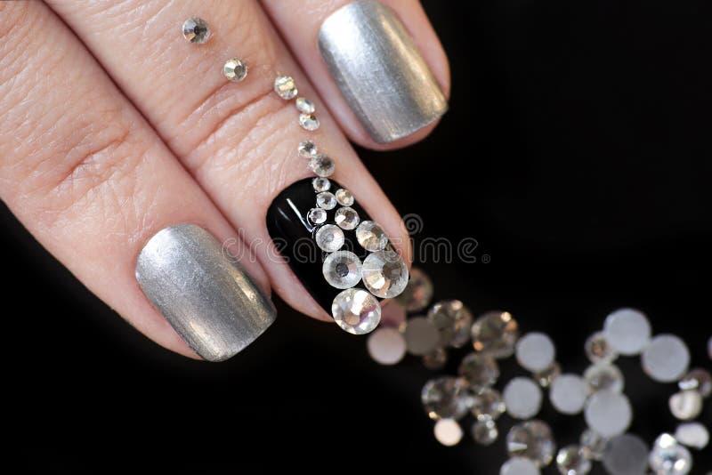 Zwarte zilveren manicure op korte spijkers met een ontwerp stock afbeelding