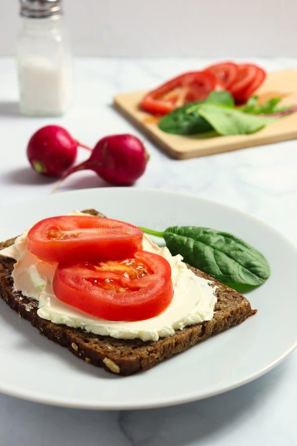 Zwarty żyto chleb z śmietankowymi sera i pomidoru plasterkami obrazy royalty free