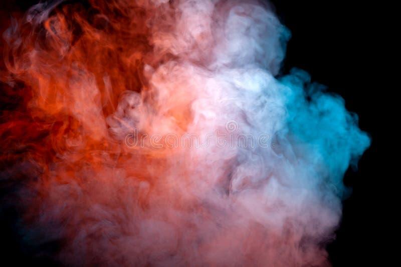 Zwarty, wirujący chmurę kolorowy dym przeciw czarnemu tłu, podkreślającą w czerwonym i błękitnym w falach od vape obraz stock