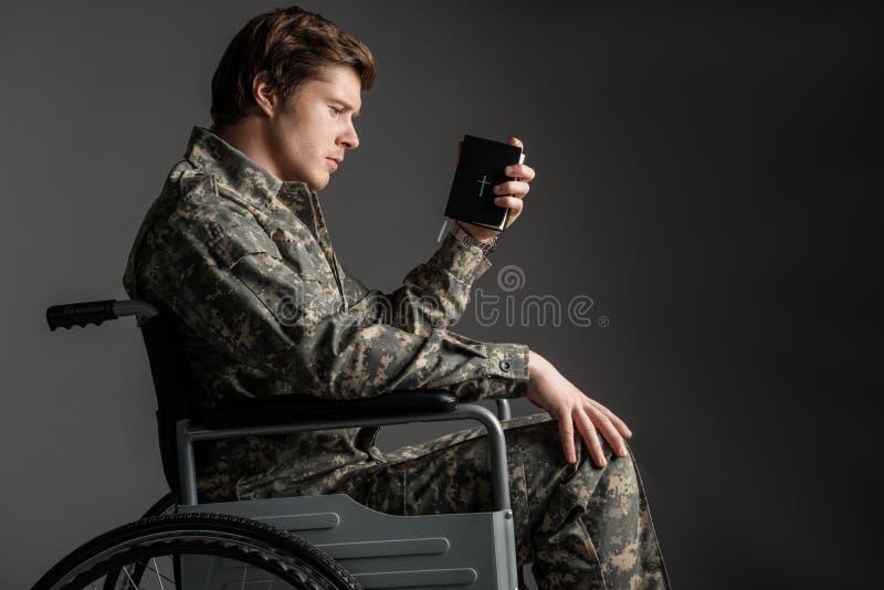 Zwarzony niepełnosprawny młody człowiek trzyma biblię fotografia stock