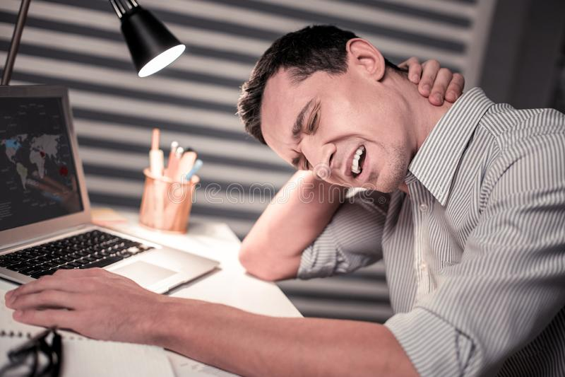 Zwarzony nieszczęśliwy przystojny mężczyzna dotyka jego szyję fotografia royalty free