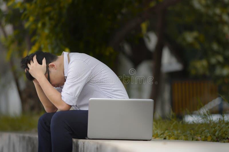 Zwarzony zadumany Azjatycki biznesowy mężczyzna w formalnej odzieży cierpieniu od stresu na zewnątrz przy biurem zdjęcie stock
