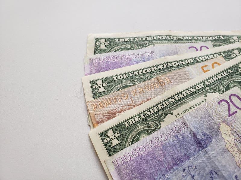 Zweedse bankbiljetten en Amerikaanse dollarrekeningen op witte achtergrond stock afbeeldingen