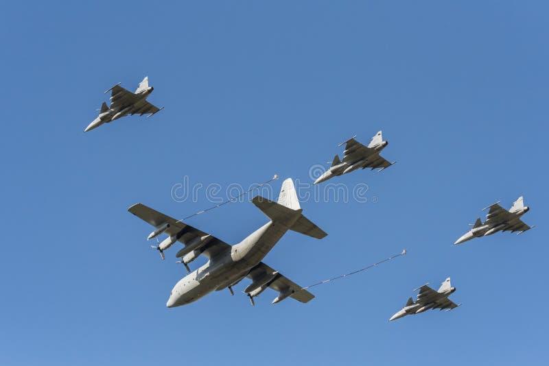 Zweedse c-130 Hercules-tanker en vier Gripen-vechters stock afbeeldingen