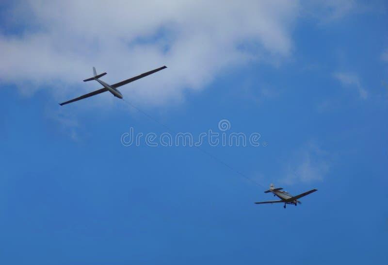 Zweefvliegtuig aan een vliegtuig wordt vastgehaakt dat stock foto's