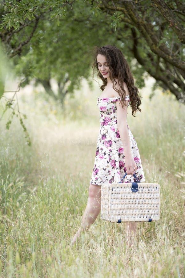 Zweet jonge vrouw die een retro picknickmand houden stock foto's