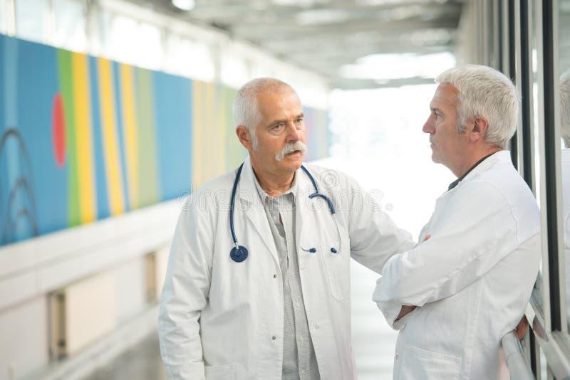 Zwei ältere Doktoren, die im hospotal Korridor sprechen lizenzfreie stockfotos