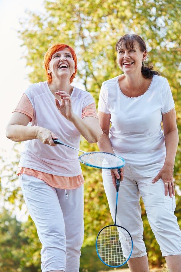 Zwei ältere Frauen, die den Spaß spielt Badminton haben lizenzfreie stockfotografie