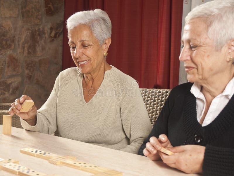 Zwei ältere Frauen, die Dominos spielen stockbild