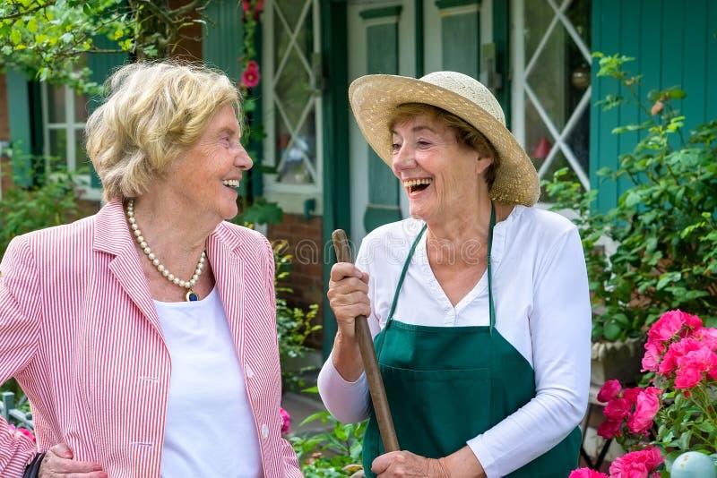 Zwei ältere Frauen, die zusammen im Garten lachen stockfotografie
