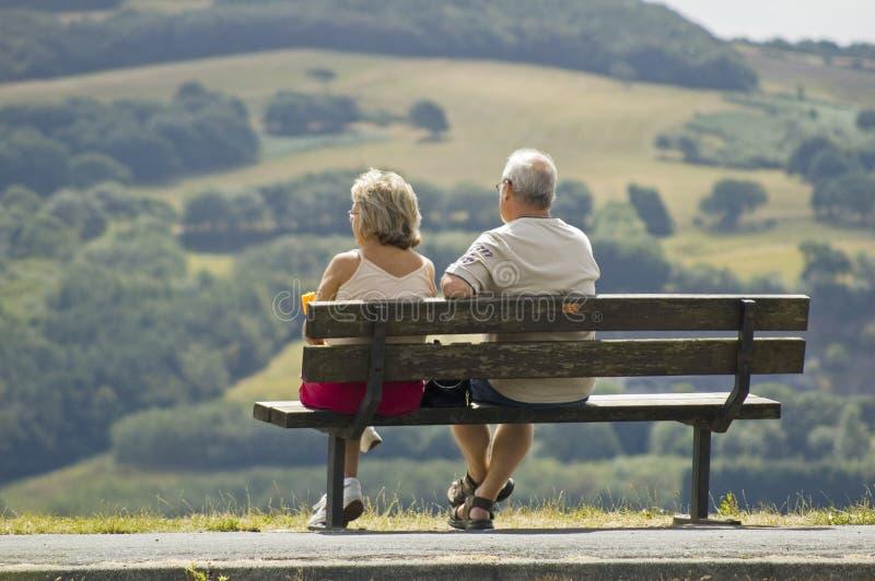 Zwei ältere Leute, die auf einer Bank sitzen stockbilder