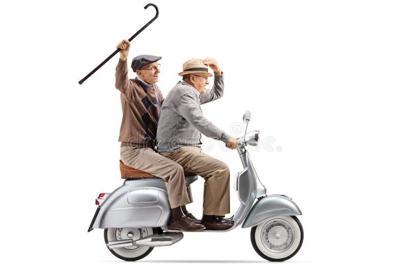 Zwei ältere Männer, die einen Weinleseroller reiten und mit einem Stock wellenartig bewegen stockbild