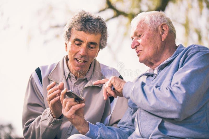 Zwei ältere Männer, die intelligentes Telefon im Park verwenden stockbild