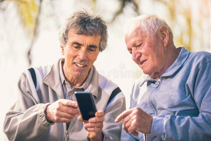 Zwei ältere Männer, die intelligentes Telefon verwenden lizenzfreie stockfotografie