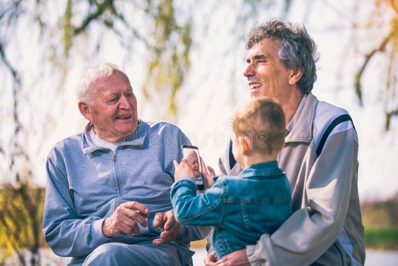 Zwei ältere Männer und Enkel, der intelligentes Telefon verwendet lizenzfreie stockfotos