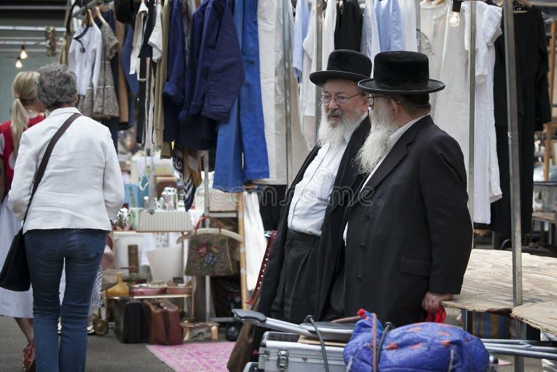 Zwei ältere orthodoxe jüdische Männer mit den Bärten, die schwarze Mäntel tragen lizenzfreie stockbilder