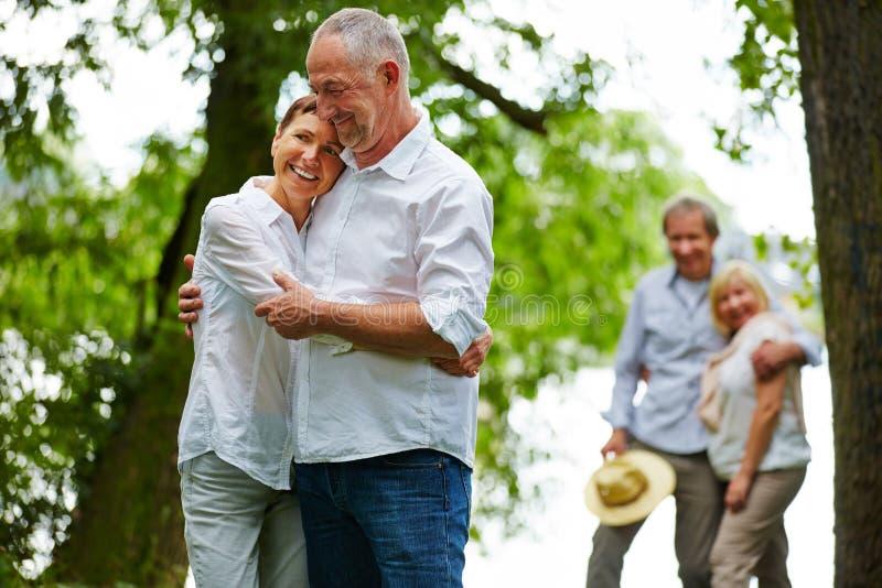 Zwei ältere Paare im Garten des Ruhesitzes stockbilder