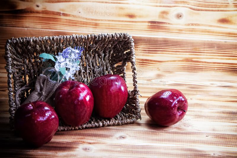 Zwei Äpfel und getrocknete Blüten, in einen Korb eingeflochten, neben dem verschwommenen roten Apfel auf Holzbrett lizenzfreie stockfotografie