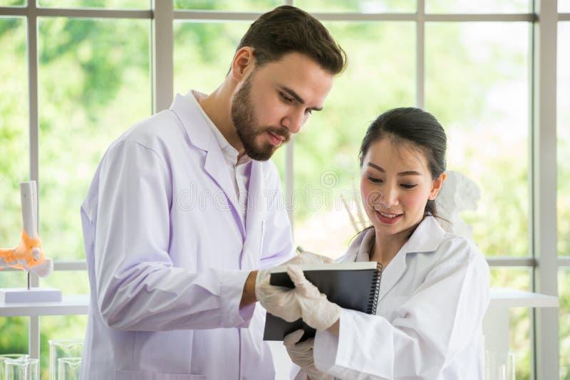 Zwei Ärzte, die mit Papier am Krankenhaus sich beraten lizenzfreie stockfotos