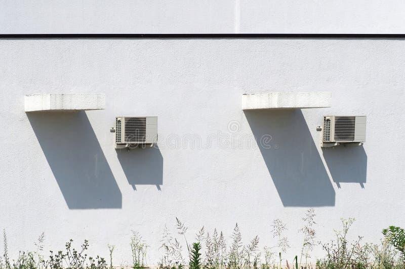 Zwei ÄußerKlimaanlagen und ihre langen Schatten auf einer Ausgangsweißen Wand, unter einem sonnigen Tag des heißen Sommers lizenzfreies stockfoto