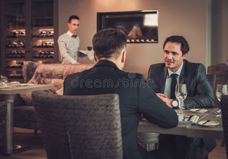 Zwei überzeugte Geschäftsleute essen Business-Lunch am Restaurant zu Mittag lizenzfreies stockbild