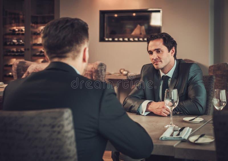 Zwei überzeugte Geschäftsleute essen Business-Lunch am Restaurant zu Mittag lizenzfreie stockfotos