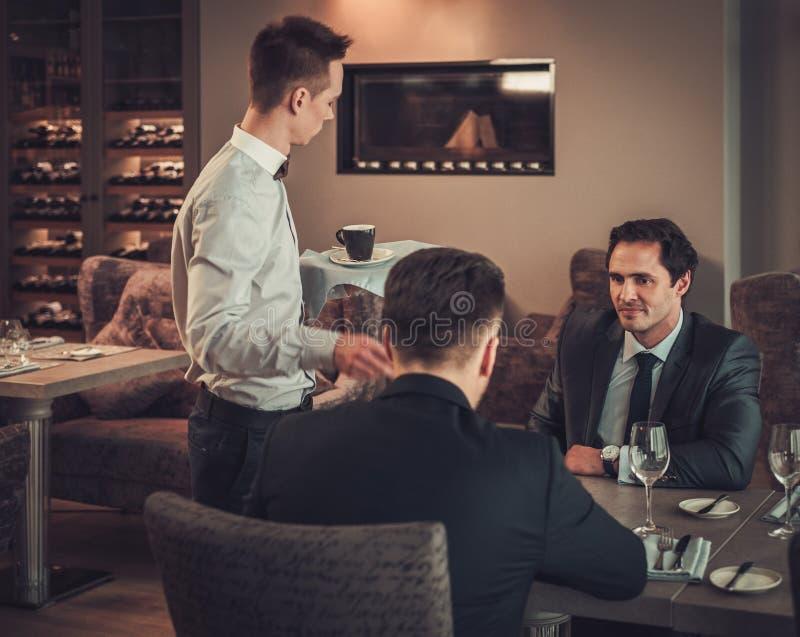 Zwei überzeugte Geschäftsleute essen Business-Lunch am Restaurant zu Mittag stockfotografie