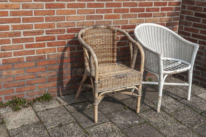 Zwei abgenutzte geflochtene Stühle, die eine umgebene Wand bereitstehen stockbild
