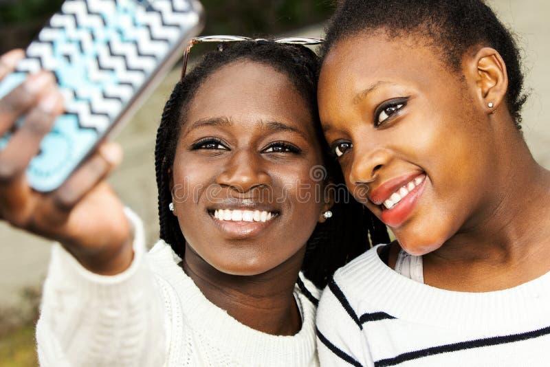 Zwei afrikanischer Teenager, der selfie mit intelligentem Telefon nimmt lizenzfreies stockbild