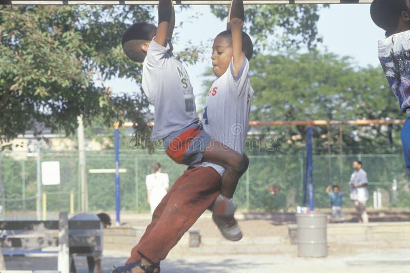Zwei afro-amerikanische Kinder, die auf Spielplatzgeräten in Chicago, IL spielen stockbild
