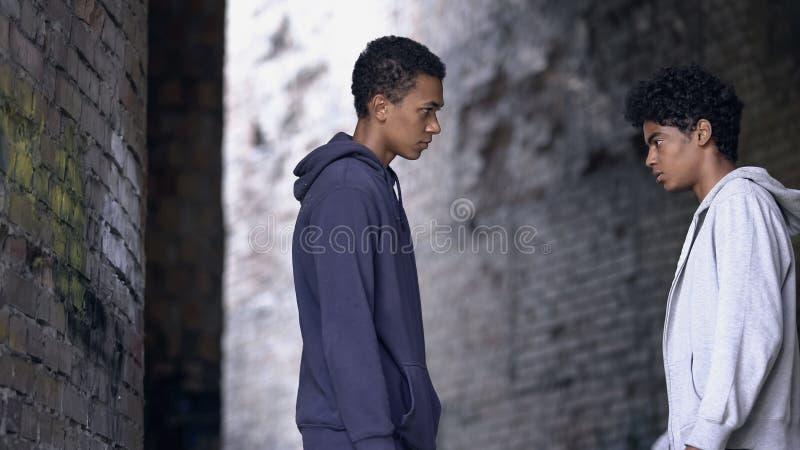 Zwei afroamerikanische Teenager, die sich gegenseitig anschauen, Konfrontationskonzept stockfotos