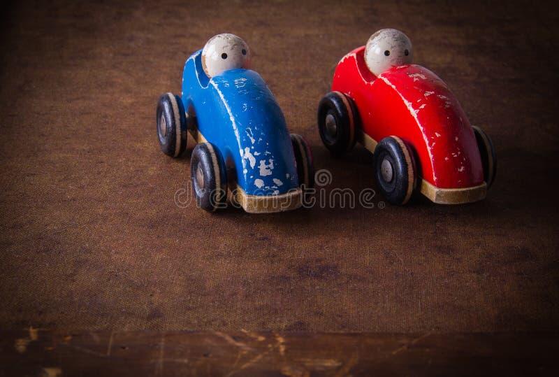 Zwei alt, einfache, natürliche, hölzerne, schädigende Spielzeugautos mit Puppen stockbild