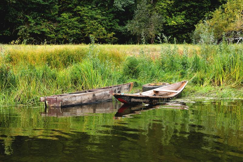 Zwei alte Boote auf dem Ufer werden an einem alten Autorad, auf einem Hintergrund des grünen Grases gebunden stockfoto