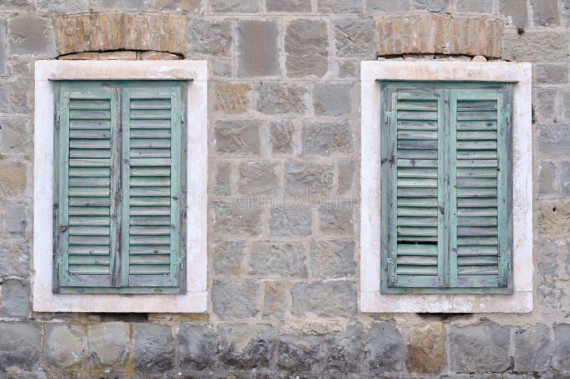 Zwei alte Fenster mit geschlossenen Fensterläden auf einem alten Haus stockbilder