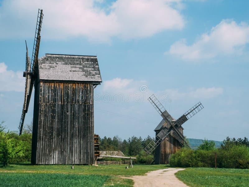 Zwei alte hölzerne Windmühlen in der Landschaft lizenzfreies stockbild
