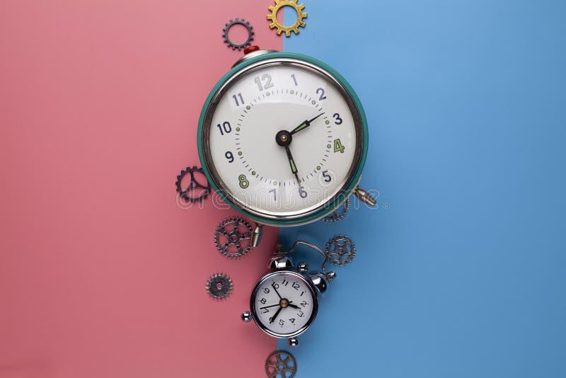 Zwei alte Wecker und kleine Gänge, Teile der Uhr auf einem zwei-farbigen Hintergrund lizenzfreies stockfoto